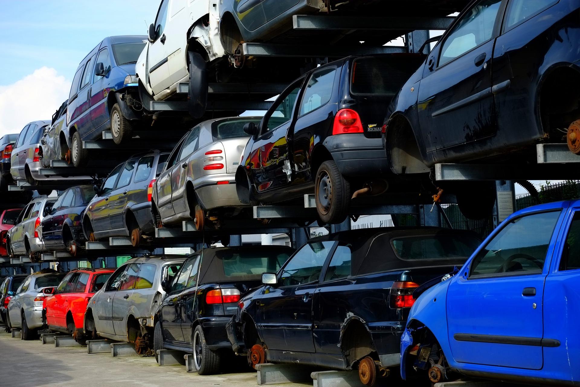Zezłomowane pojazdy ułożone w rzędy i stosy